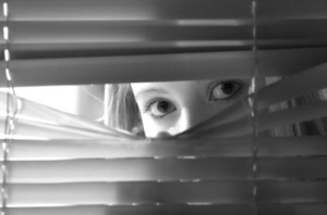 Young female looking through window blinds at night.(shallow depth of field)