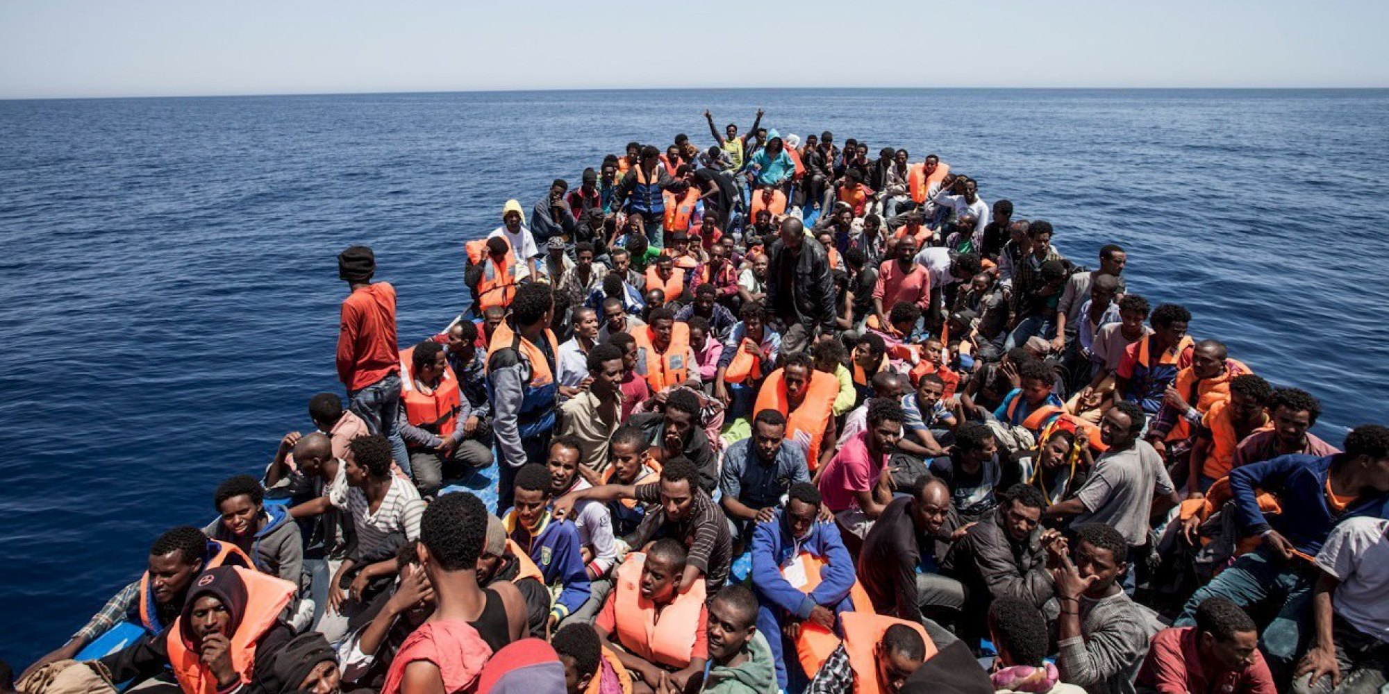 Migrants crowd the deck of their wooden boat off the coast of Libya